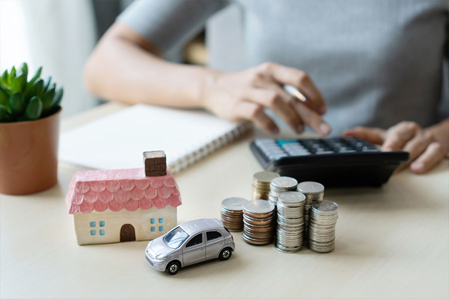 Home and Auto Insurance (Bundled) - Picture of a Woman's Hands with a House and Car on the Desk