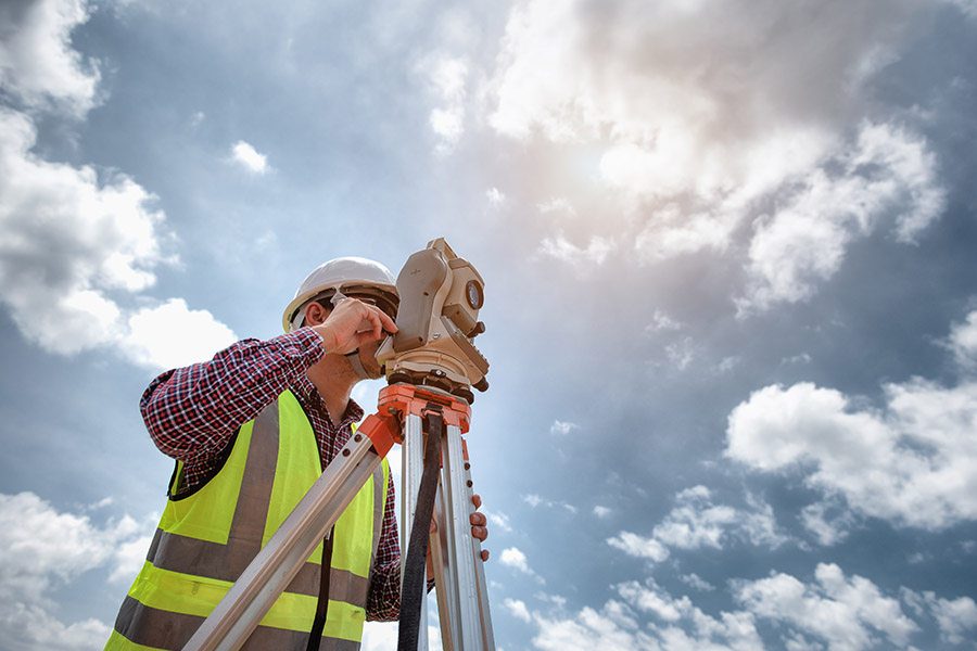 Land Surveyor Insurance - Worker Looking Over Land to Survey with a Bright Blue Sky