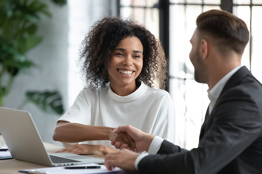 Investment Advisor Insurance - Smiling Woman Shaking Hands With Her Advisor at an Investment Meeting