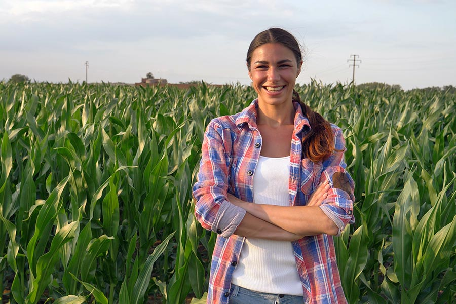 Business Insurance - Farmer Standing In Her Corn Field With Her Arms Crossed Looking Proud